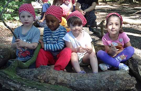 Kinder vor Baumstamm
